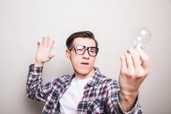 jonge mens die in glazen kleine gloeilamp houden Stock Afbeelding