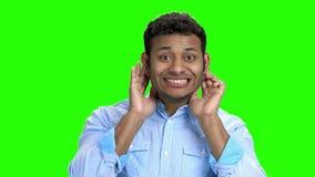 Jonge mens die grappig gezicht op het groene scherm maken stock videobeelden