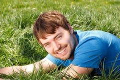 Jonge Mens die in Gras legt Stock Fotografie