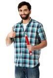 Jonge mens die groot rood potlood houden stock foto