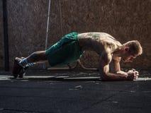 Jonge mens die in gymnastiek oefeningen voor abs doen royalty-vrije stock foto's