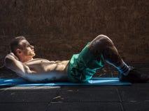 Jonge mens die in gymnastiek oefeningen voor abs doen royalty-vrije stock fotografie