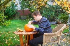 Jonge mens die Halloween pompoen maakt Royalty-vrije Stock Afbeeldingen