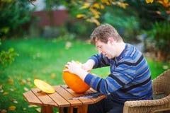Jonge mens die Halloween pompoen maakt Royalty-vrije Stock Afbeelding