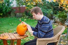 Jonge mens die Halloween pompoen maakt Stock Afbeeldingen