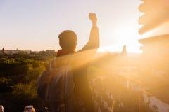 Jonge mens die handen opheffen omhoog tegen zonlicht - vermelde succes, voltooiing en overwinning stock afbeelding