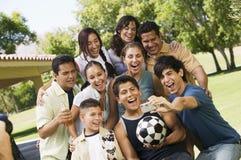 Jonge mens die het digitale camera fotograferen gebruiken zelf met jongens (13-15) vrienden en familie. Stock Fotografie