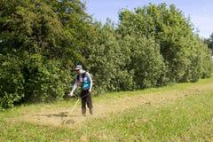Jonge mens die het gras maaien Royalty-vrije Stock Afbeeldingen