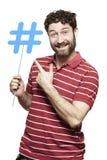 Jonge mens die het sociale media teken glimlachen houden Stock Afbeeldingen