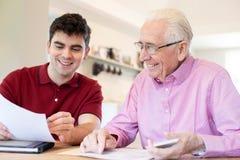 Jonge Mens die Hogere Buur met Administratie thuis helpen stock afbeelding