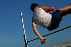 Jonge mens die in hoogspringen concurreert stock foto's