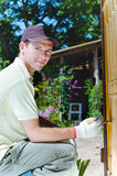 Jonge mens die houten omheining in de tuin schildert Royalty-vrije Stock Foto's