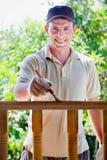 Jonge mens die houten omheining in de tuin schildert Stock Fotografie