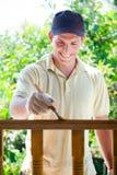 Jonge mens die houten omheining schildert Stock Afbeeldingen