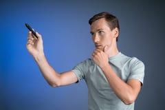 Jonge mens die iets met een naald op het transparante scherm, malplaatje voor collage schrijven stock foto's