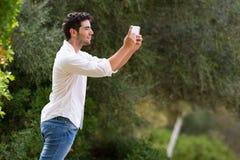 Jonge mens die Internet-dekking zoeken openlucht Stock Fotografie