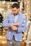 Jonge mens die jasje in kledingsopslag proberen Royalty-vrije Stock Fotografie