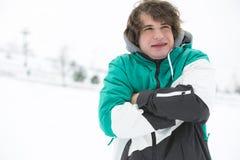 Jonge mens die in jasje in sneeuw rillen Royalty-vrije Stock Afbeeldingen