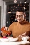 Jonge mens die ketchup toevoegen aan het voedsel terwijl het houden van de eetstokjes met andere hand stock afbeelding