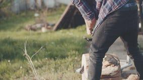 Jonge mens die kettingzaag in tuin met behulp van stock footage