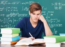 Jonge mens die in klaslokaal bestuderen stock afbeeldingen