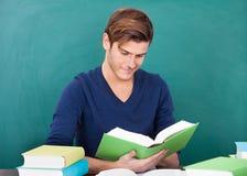 Jonge mens die in klaslokaal bestuderen royalty-vrije stock afbeelding