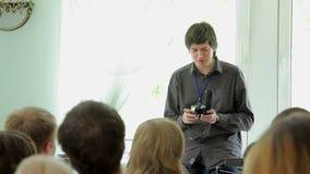 Jonge mens die in klasse met op de microfoon van het camerajachtgeweer in handen spreken stock video