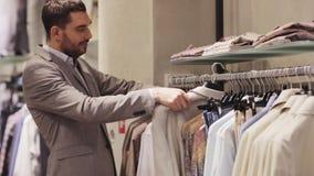 Jonge mens die kleren in kledingsopslag kiezen stock videobeelden
