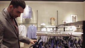 Jonge mens die kleren in kledingsopslag kiezen stock video