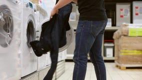 Jonge mens die kleren nemen uit wasmachine in grote opslag Grappige video stock video
