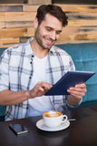 Jonge mens die kop van koffie hebben die tablet gebruiken Stock Afbeeldingen