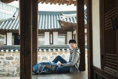 Jonge mens die in Korea reizen Koreaans traditioneel huis stock afbeeldingen