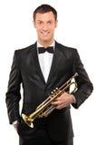 Jonge mens die in kostuum een trompet houdt Royalty-vrije Stock Fotografie