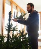 Jonge mens die kunstmatige Kerstboom opzetten Royalty-vrije Stock Afbeelding