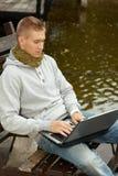 Jonge mens die laptop computer in openlucht met behulp van Royalty-vrije Stock Afbeeldingen