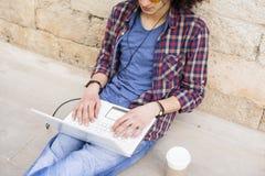 Jonge mens die laptop en hoofdtelefoons met behulp van Royalty-vrije Stock Fotografie
