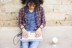 Jonge mens die laptop en hoofdtelefoons met behulp van Royalty-vrije Stock Afbeelding