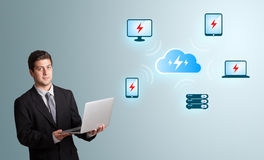 Jonge mens die laptop houden en wolk gegevensverwerkingsnetwor voorstellen Stock Foto's