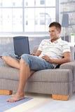 Jonge mens die laptop met behulp van die thuis glimlacht Royalty-vrije Stock Fotografie