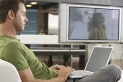 Jonge Mens die Laptop in Moderne Flat met behulp van royalty-vrije stock afbeeldingen