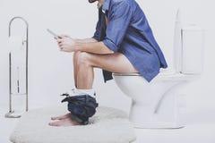 Jonge mens die laptop op toilet met behulp van royalty-vrije stock fotografie