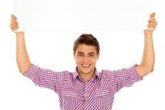 Jonge mens die lege affiche houdt Stock Foto