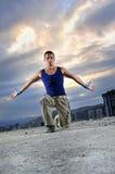 Jonge mens die in lucht openlucht bij nacht springt Stock Fotografie