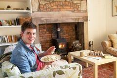Jonge mens die maaltijd eet door brand royalty-vrije stock afbeelding