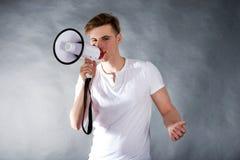 Jonge mens die in megafoon schreeuwen Stock Fotografie