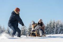 Jonge mens die meisjes op de winterslee trekken Royalty-vrije Stock Afbeeldingen