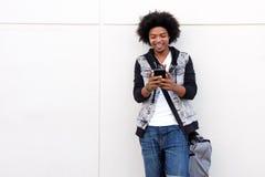 Jonge mens die met afro celtelefoon bekijken Stock Foto