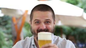 Jonge mens die met baard schuimend bier drinken stock videobeelden