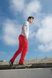 Jonge mens die met blauwe hemelachtergrond met een skateboard rijden Stock Afbeeldingen