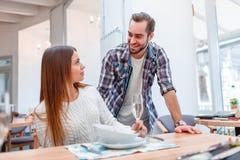 Jonge mens die met jonge dame in een restaurant flirten stock afbeeldingen